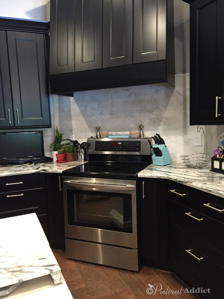 Finished subway marble backsplash - black ikea kitchen - black and white granite countertops