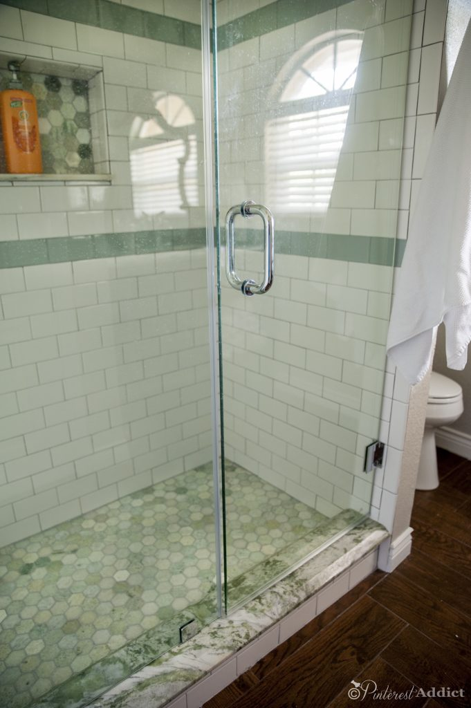 Guest bathroom makeover - subway tile, green marble mosaic, frameless shower doors