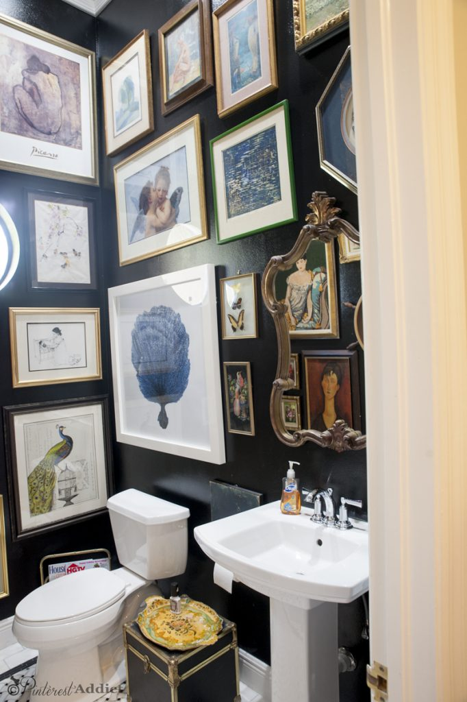Black trunk used for toiletry storage - black bathroom with art gallery walls. Art Gallery Bathroom - gorgeous