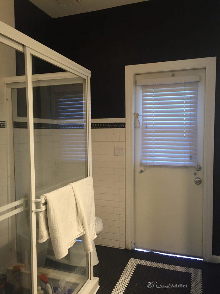 black and white bathroom - black walls, white subway, penny tile