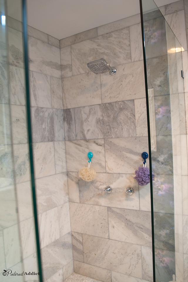 Moen Voss shower head in marble walk in shower with frameless glass doors